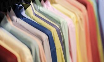 Close up of multi colored shirts on hangers photo