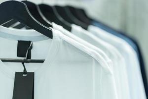 Cerca de camisetas blancas en perchas, antecedentes de prendas de vestir foto