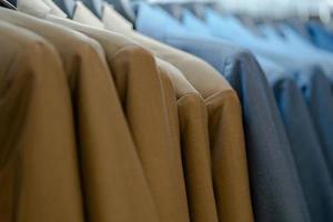 Close up of luxurious style gentlemen suit on hangers photo