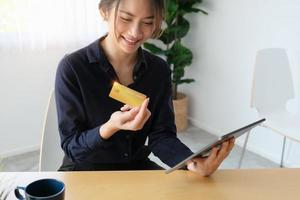 Woman looking at a credit card and holding a tablet photo