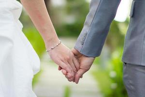 Bride and groom married couple holding hands in wedding ceremony photo