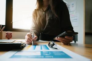 Cerca de la mano de la empresaria sosteniendo un lápiz y papeleo financiero con diagrama de red financiera. foto