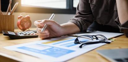 joven contable equipo de marketing que consulta y utiliza una calculadora para analizar el crecimiento de las ventas en el mercado laboral global. concepto de contabilidad foto