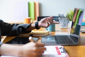 Cerrar la mano de la empresaria apuntando y analizando gráficos con una computadora portátil foto