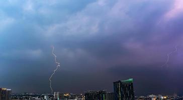 tormenta eléctrica relámpago sobre la ciudad al atardecer foto
