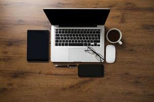 espacio de trabajo con computadora portátil, teléfono inteligente, tableta, taza de café, gafas y bolígrafo foto