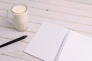 The notebook and a glass of milk are on the desk photo