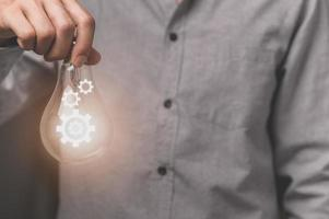 A business man's hand holds a light bulb with a gear icon photo