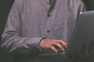 A standing man using a laptop computer photo