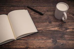 Notebook and a glass of milk on the desk photo