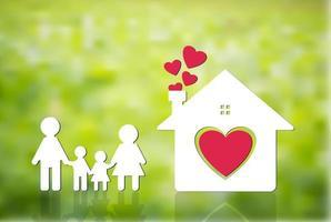 familia feliz en casa, mamá y papá están tomados de la mano con niños y niñas. Corazón de casa en el suelo, fondo verde borroso vector