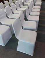 Rows of white chairs in a hotel photo