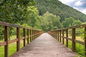 Puente de madera sobre un campo con prados y colinas boscosas foto