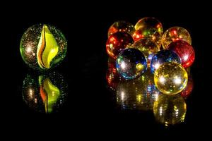 Mirrored colourful glass beads on black background photo