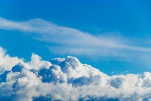 White fluffy cumulus clouds against a blue sky photo