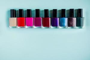Palette of bright nail polishes on blue background photo