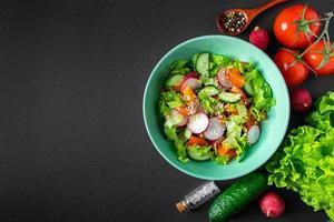 Ensalada de verduras frescas en un cuenco de cerámica sobre fondo gris foto