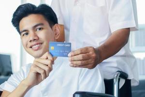 Paciente masculino sentado en una silla de ruedas en un hospital tiene una tarjeta de crédito foto