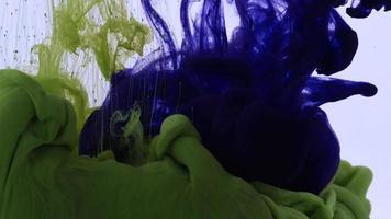 Résumé des gouttes d'encre de couleur vert vif et bleu foncé se répandant dans la texture de l'eau. video