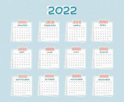 Horizontal Calendar for 2022 from January to December. Every month is on squared paper with dots, piece of newspaper is at the bottom, pink scotch, color patterned adhesive tape is on the top vector