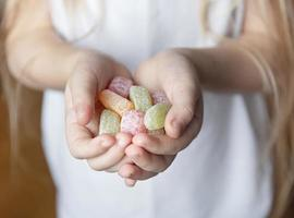 Child holding candy,  jelly in hand photo