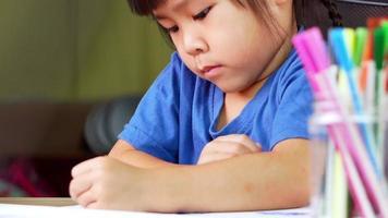 niña dibujando un arco iris y un árbol con lápices de colores en la mesa video