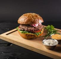 Tasty cheeseburger on wooden board ready be served photo