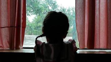 Silueta trasera de niña triste mirando por la ventana en un día lluvioso video