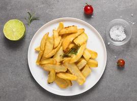 Vista superior de papas fritas en un plato con sal y tomates foto