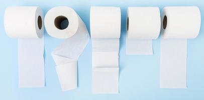 Vista superior de rollos de papel higiénico desplegado sobre fondo azul. foto
