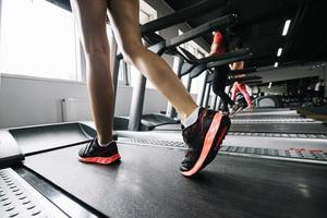 Woman wearing sneakers using treadmill photo