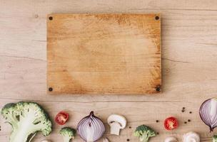 tabla de cortar de madera con brócoli, tomates, cebolla, champiñones y pimienta negra foto