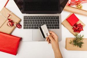 Woman buying Christmas presents online with gifts on table photo