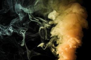 Yellow dense fume smoke on abstract black background photo