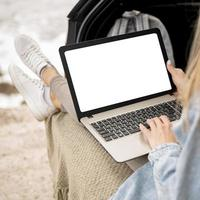 Young woman browsing laptop on road trip photo