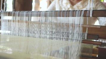 Mujer asiática teje tela de seda en un telar antiguo de mano video