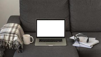 Auriculares portátiles en el sofá de casa durante la cuarentena foto