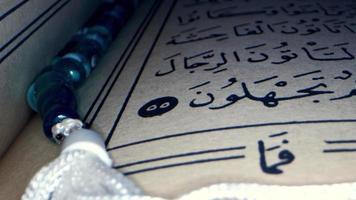una página del libro corán y rosario video