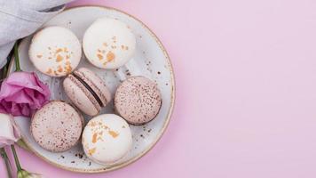 macarons en un plato con rosas y espacio de copia foto