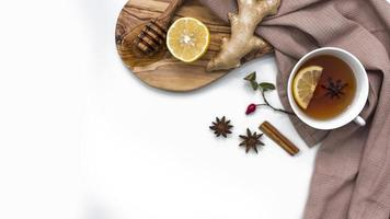 Té de limón con miel y jengibre sobre tablero de madera foto