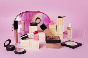 Productos de maquillaje y bolsa de cosméticos brillante sobre fondo rosa. foto