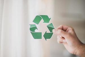 La mano del hombre que muestra el icono de reciclaje foto