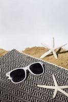 patrón de playa con gafas de sol y toalla foto