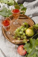 Fruit basket and wine on a picnic blanket photo