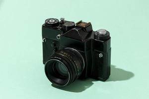 Retro black camera on green background photo