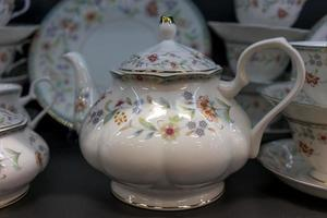 Porcelain teapot in the background of dishes photo