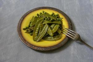 Fried green peas on a ceramic yellow plate photo