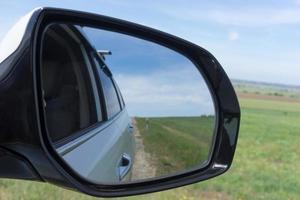 espejo de coche sobre un fondo de campos verdes. foto