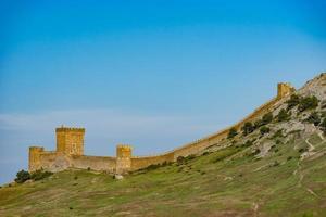 fortaleza genovesa en la cima de la montaña contra el cielo azul. foto