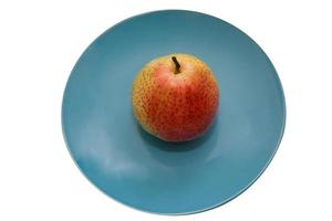 Juicy pear on a blue ceramic plate isolate on white background photo